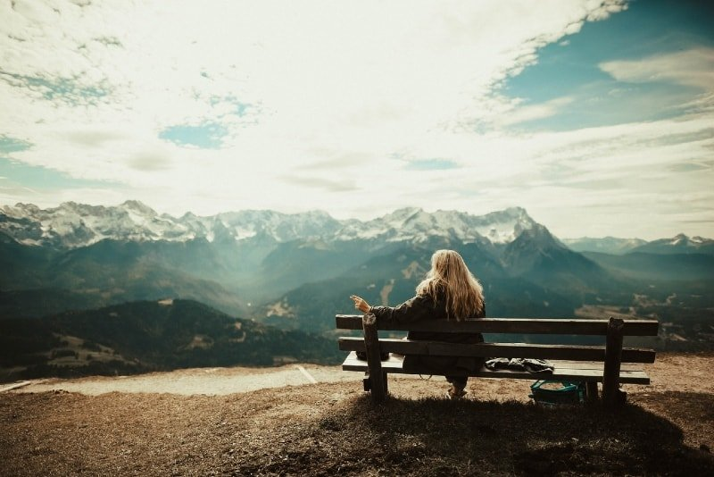 blonde woman sitting on bench looking at mountain