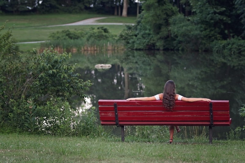 woman sitting on red bench looking at water