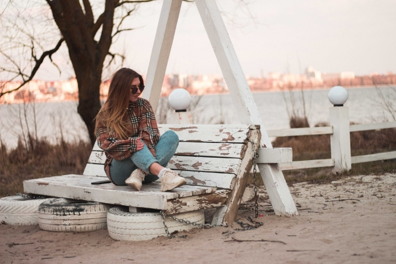 woman with sunglasses sitting on bench near river