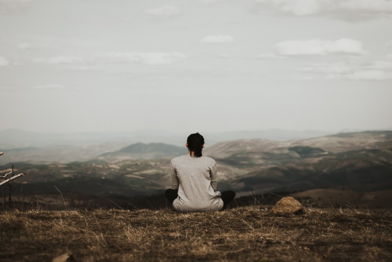 woman sitting on cliff looking at mountain