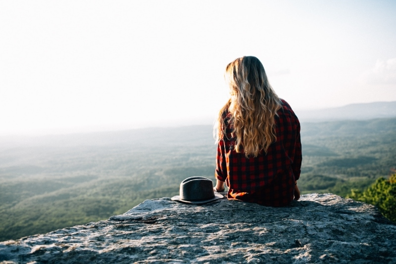 woman in black and red gingham shirt sitting on cliff