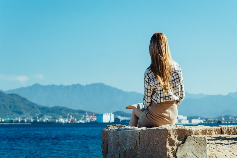 woman sitting on concrete surface looking at sea