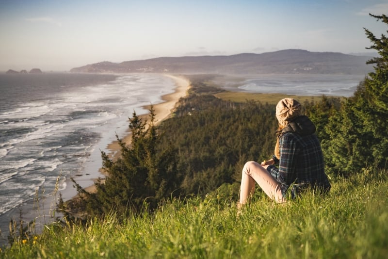 woman sitting on grass looking at ocean