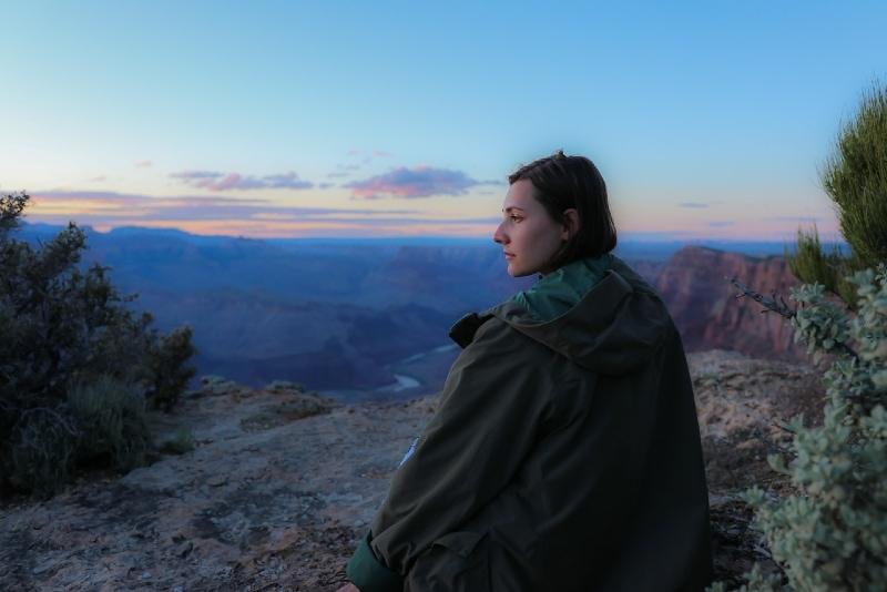woman in green jacket sitting on rock