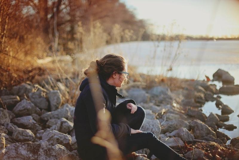 woman sitting on rocks near water