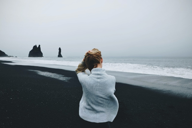 woman in gray sweater sitting on shore