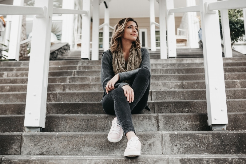woman with gray scarf sitting on stairs