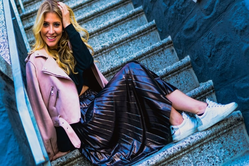 smiling woman in pink jacket sitting on stairs
