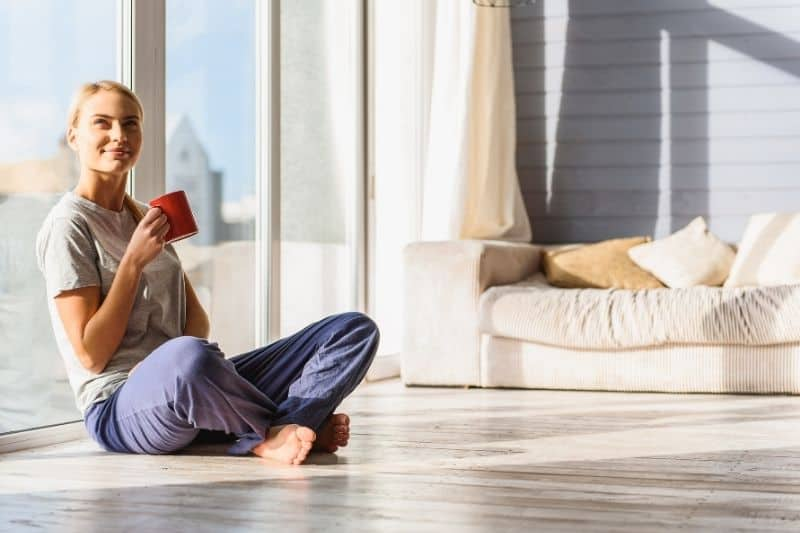 woman sitting on the floor sipping coffee near the glass wall inside living room