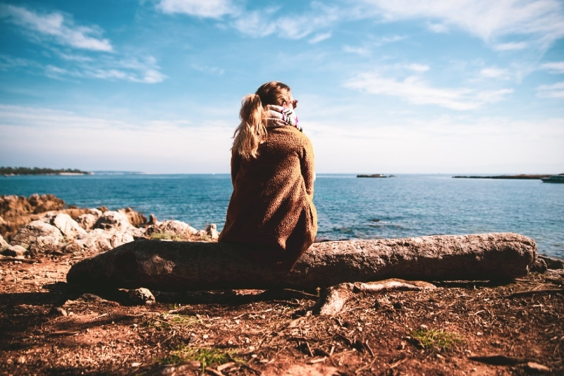 woman sitting on wood log while looking at sea