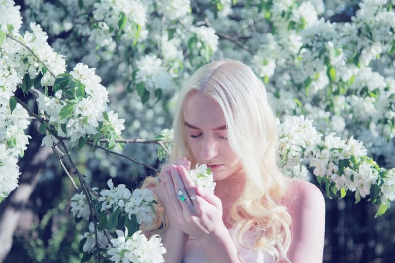 blonde woman smelling flower during daytime