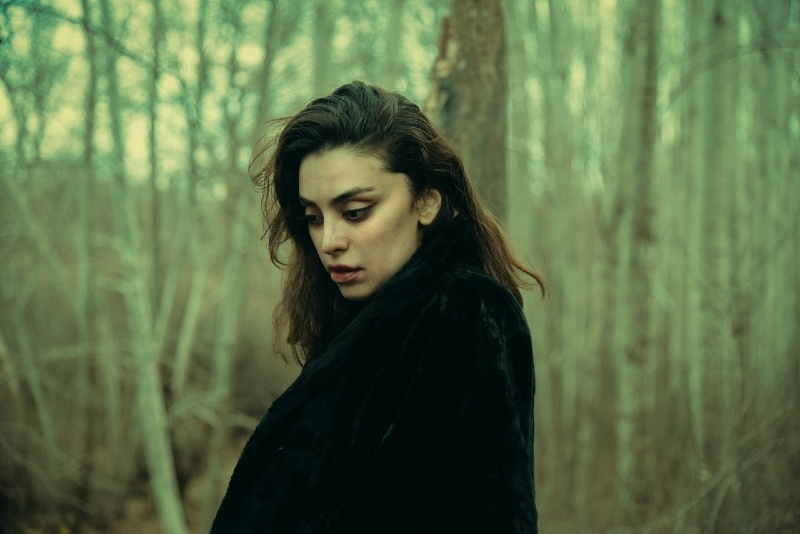 woman in black coat standing in forest