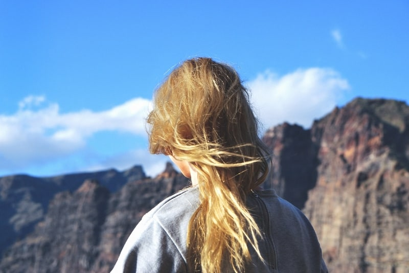 blonde woman in gray sweatshirt standing near mountain