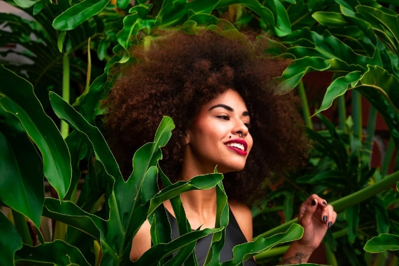 happy woman with curly hair standing near plants