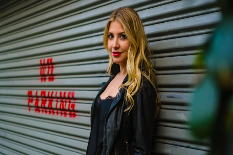 blonde woman in black jacket standing near shutter door