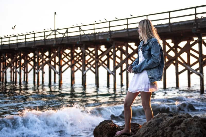 woman in denim jacket standing near water