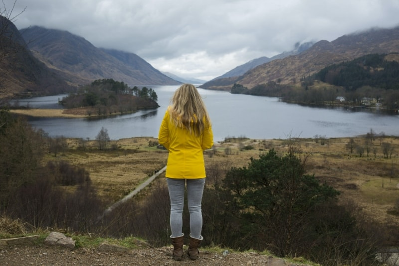 woman in yellow jacket standing near water