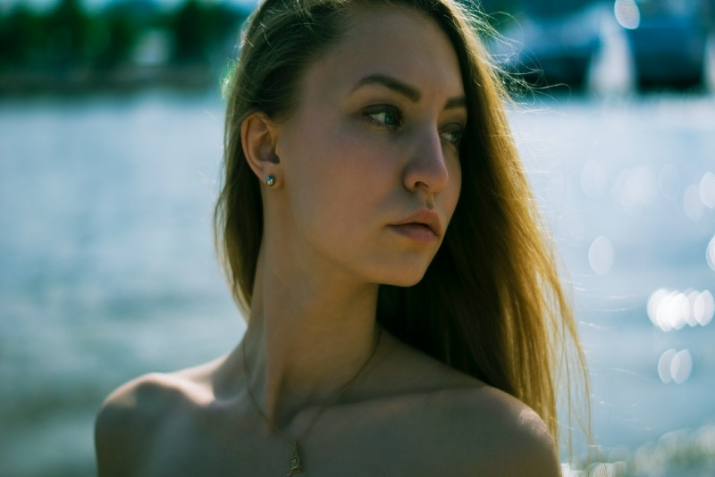 woman with golden necklace standing near water