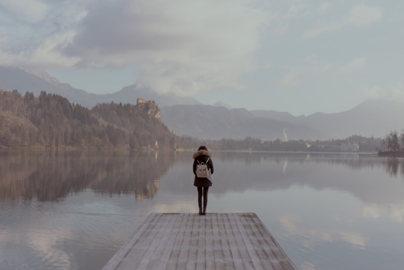 woman standing on dock looking at water