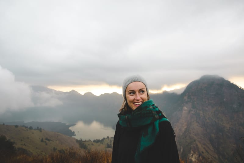 woman with green scarf standing on hill