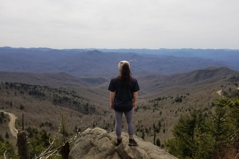 woman standing on rock looking at mountain