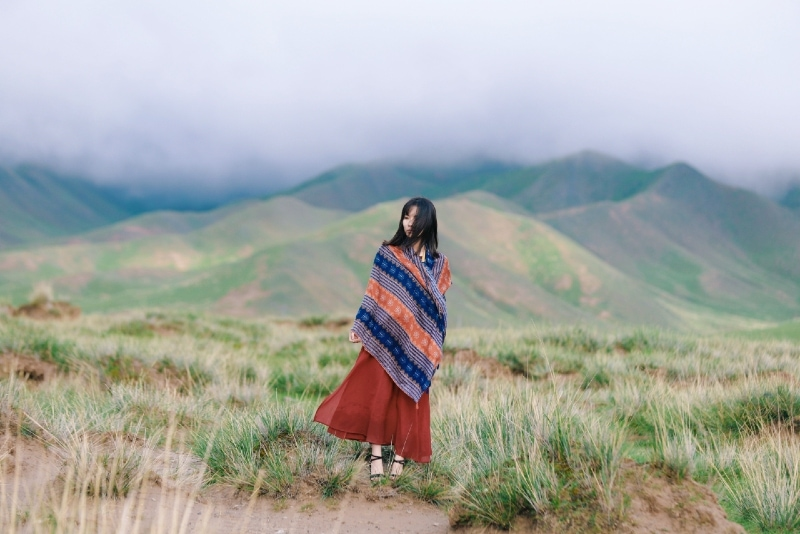 woman wrapped with scarf standing on top of mountain