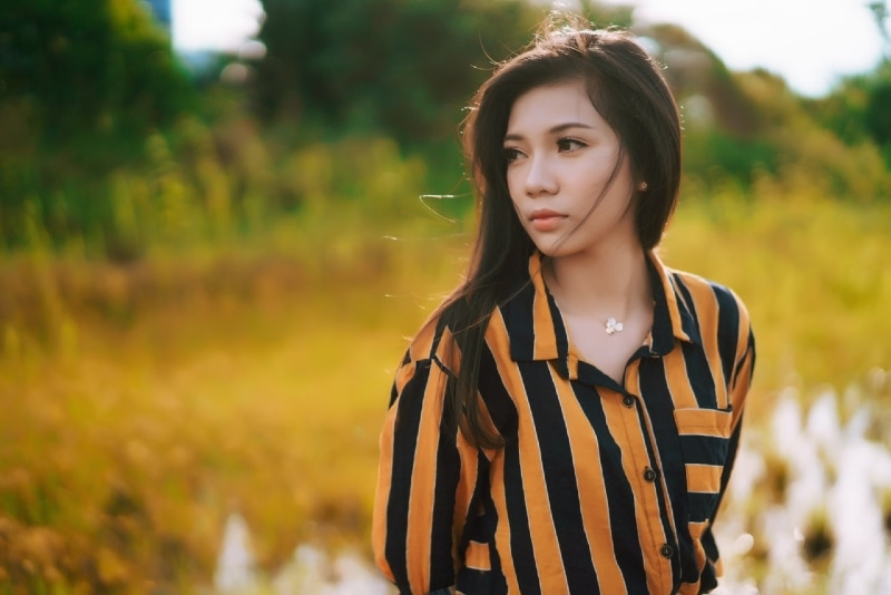 woman in yellow and black shirt standing outdoor