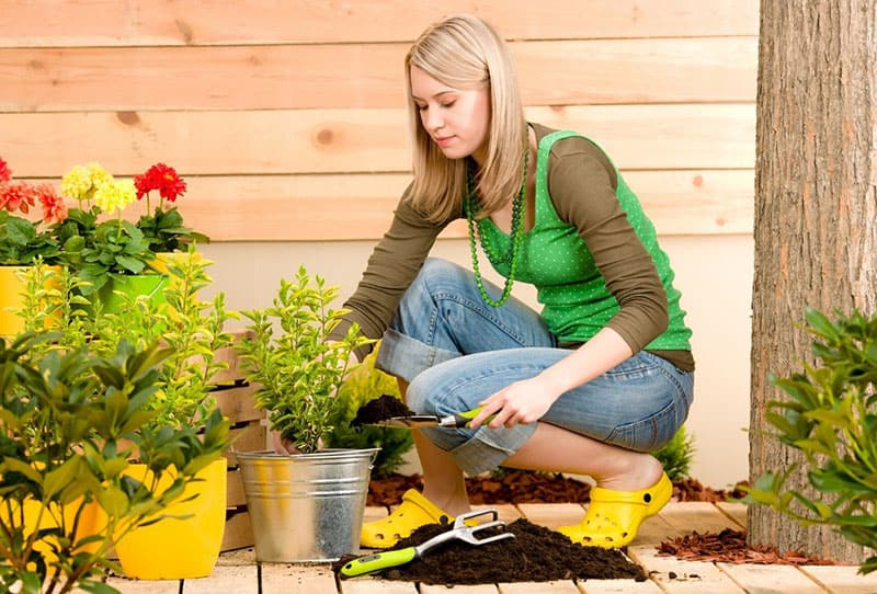 woman taking care of the plants in the porch putting soil on pot