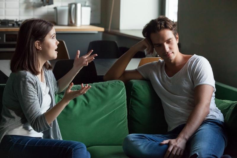 woman talking to man while sitting on green sofa
