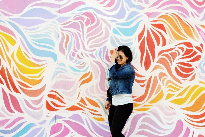 woman touching her hair while standing near colorful wall