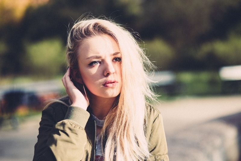 blonde woman in green jacket touching her hair outdoor