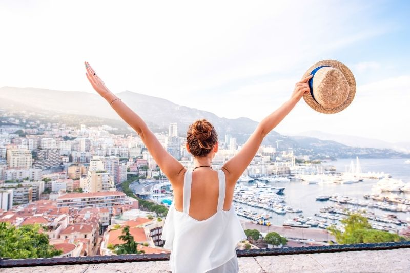 woman travelling alone in Monaco raising her hands holding her hat