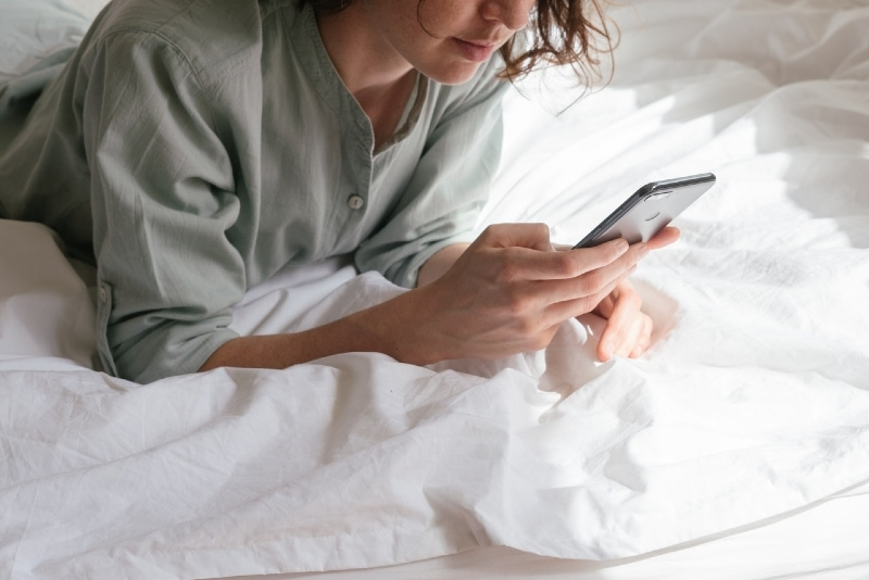 woman using smartphone while lying in bed