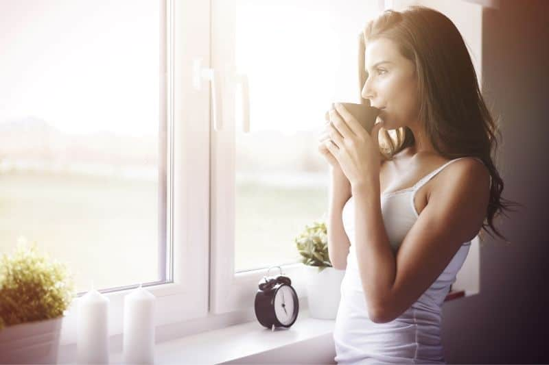 woman wakiing up with a great morning with a coffee facing outside thru the windows