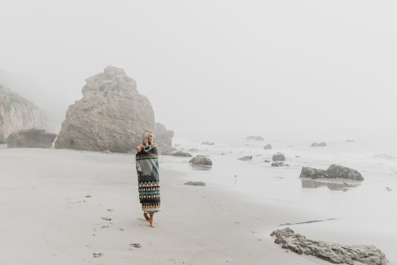 woman wrapped in blanket walking on seashore