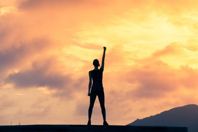 woman with fist in the air standing up with hope and courage during dusk/dawn