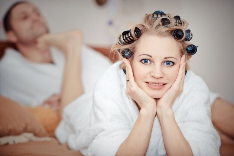 woman with hair rollers lying on bed with foot at the man's chin