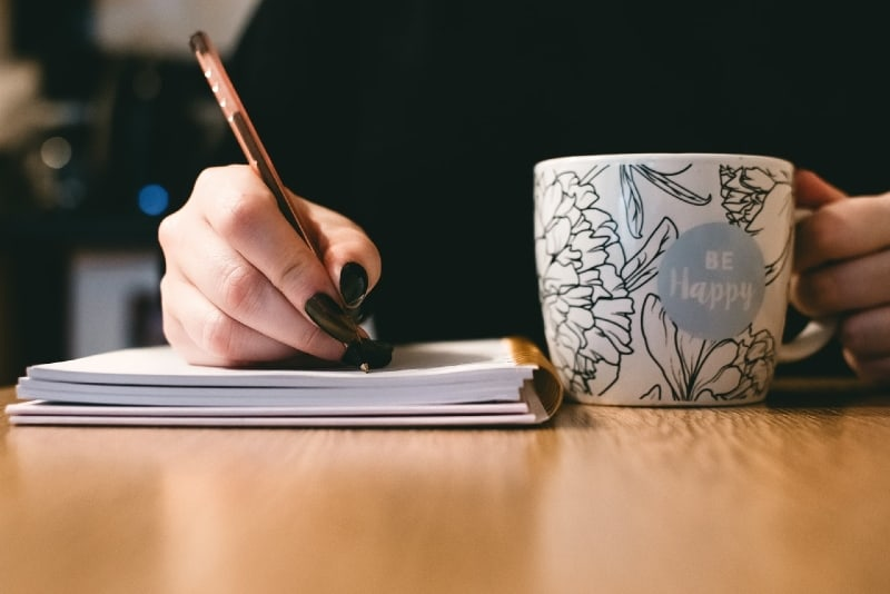 woman writing while holding ceramic mug