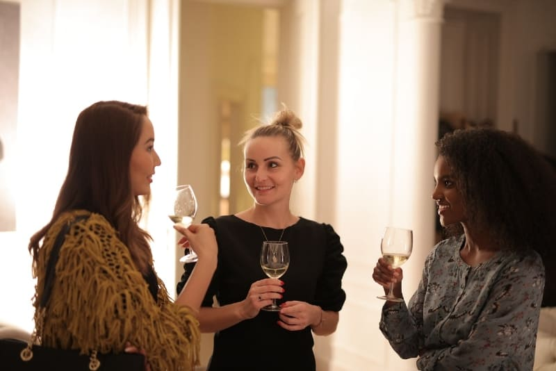 three women holding glasses of wine and talking