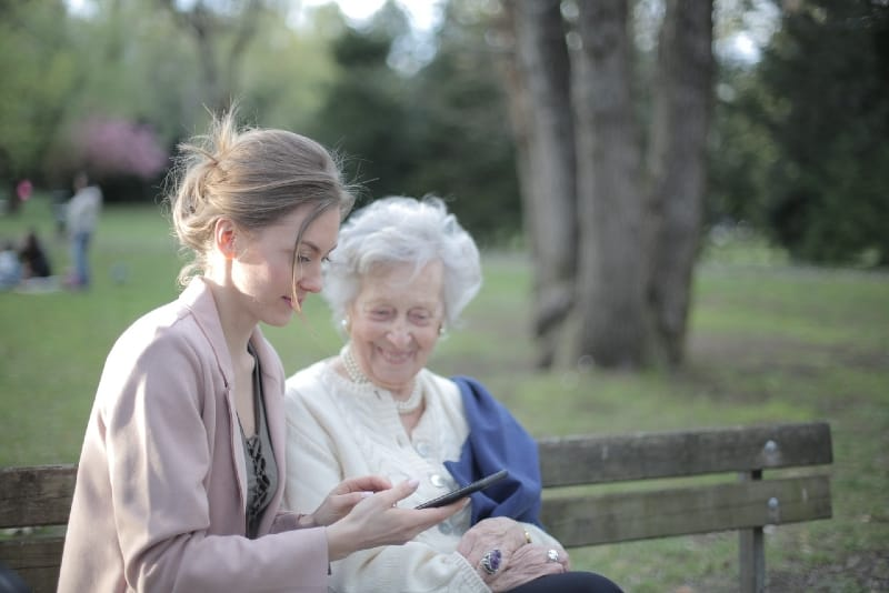 two women sitting on bench looking at smartphone