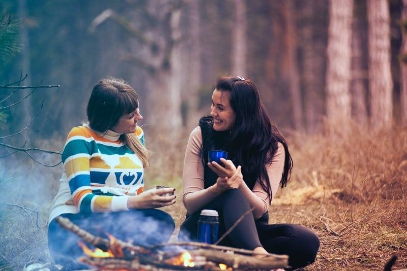 two smiling women sitting on ground near bonfire