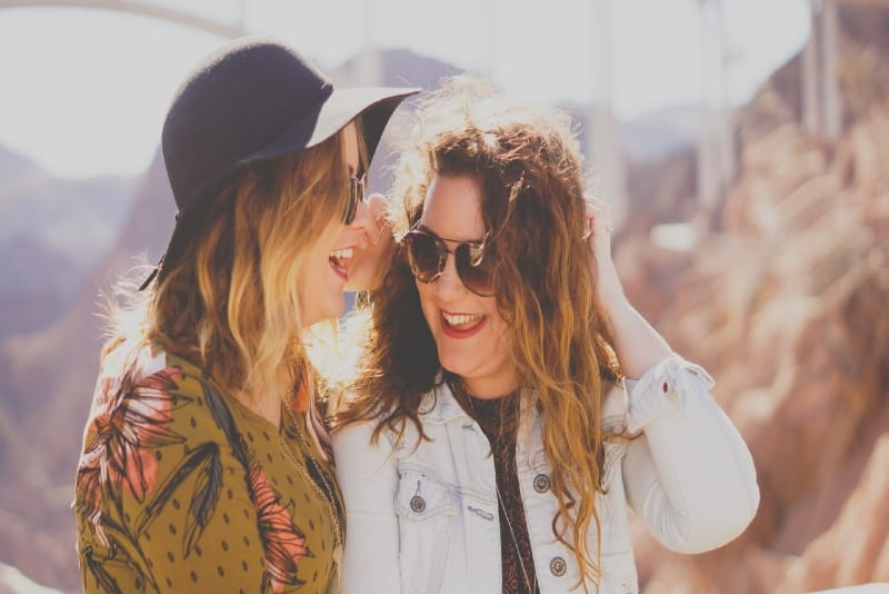 two women with sunglasses smiling outdoor