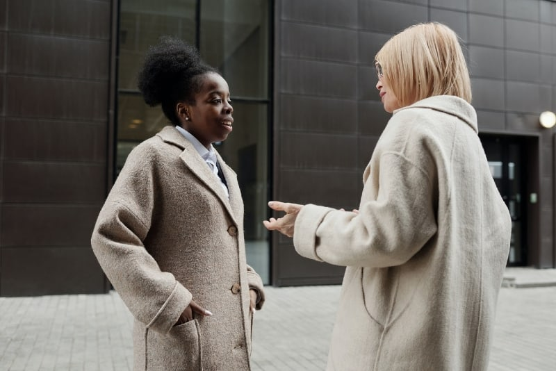 two women in beige coats talking outdoor