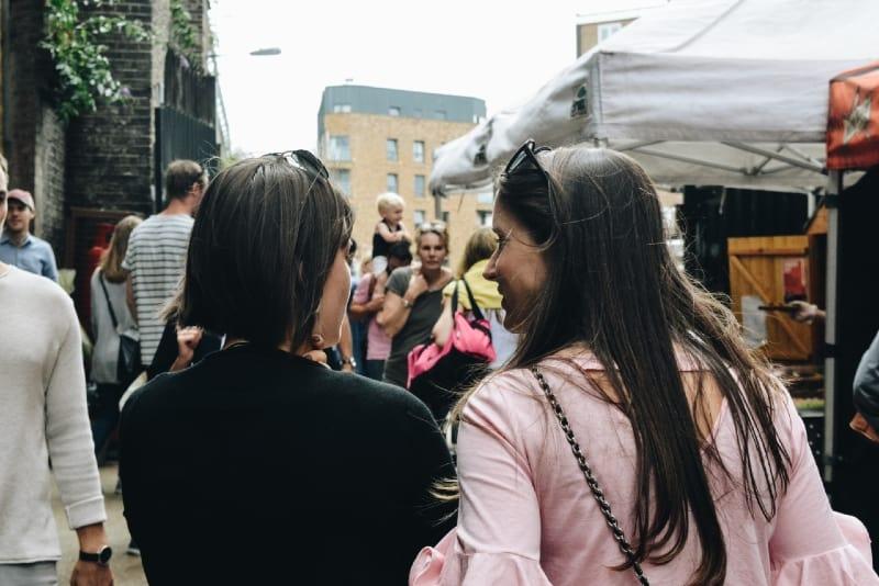 two women walking near food stalls during daytime