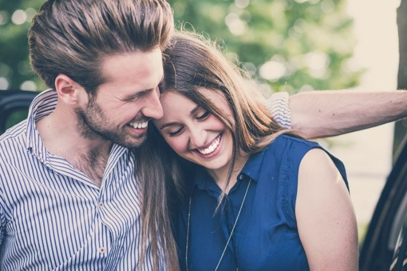 young beautiful couple smiling woman leaning on the man outdoors