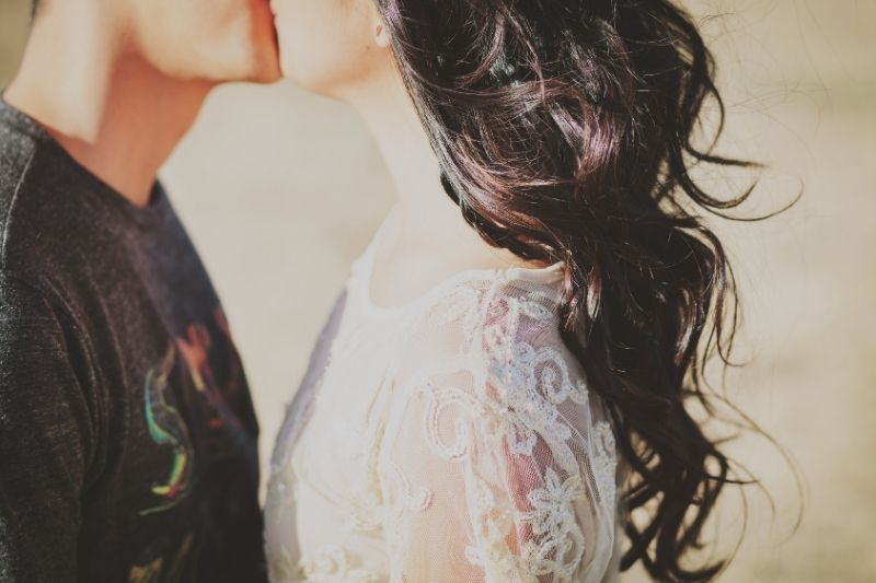 young couple kissing outdoors in cropped image