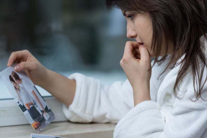 young depressed woman looking at the picture of a couple