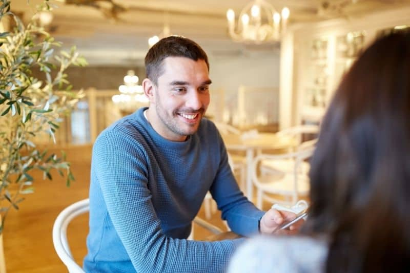 young guy talking to a woman inside a cafe