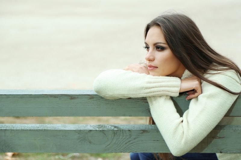 young lonely woman leaning on the bench outdoors
