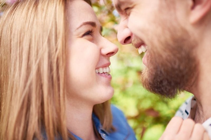 young lovers looking at each other laughing outdoors